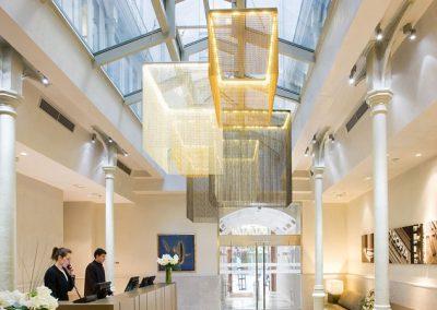 Lámpara colgante para la recepción de un hotel con estructura rectangular cayendo tiras de diferentes tonos