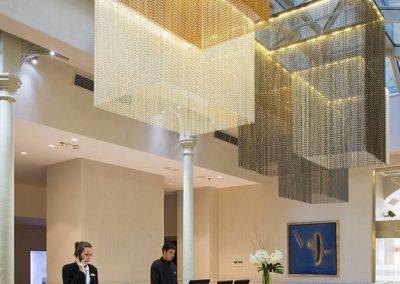 Iluminación de techo con caída de diseño para la recepción de un hotel con tonos cálidos y elegantes