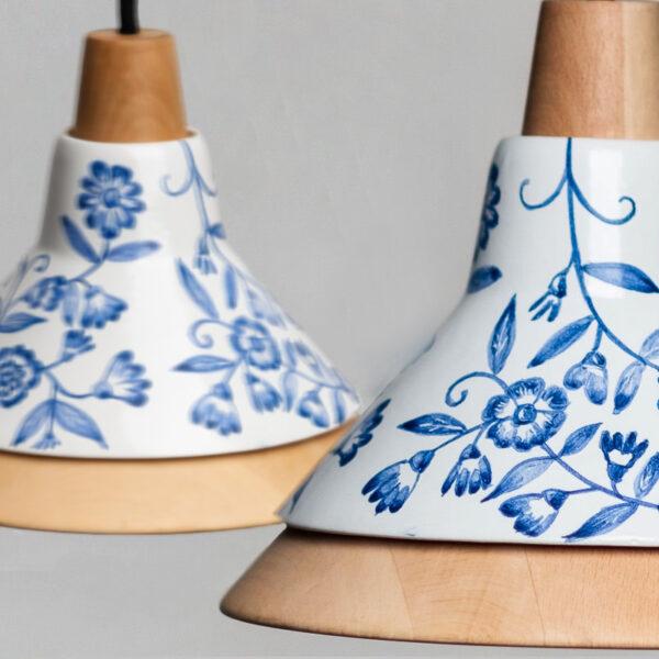 Detalle de dos lámparas hechas a mano de madera y de cerámica con adornos florales azules