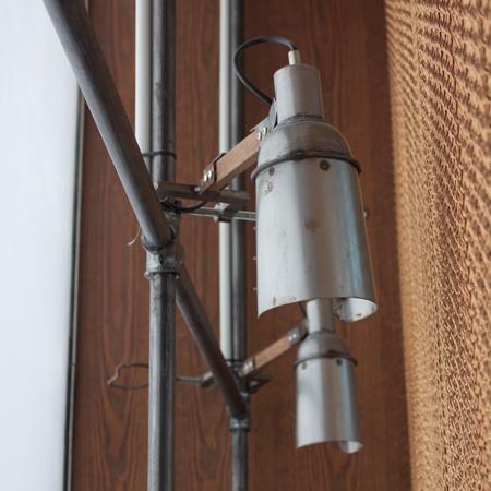 Detalle de lámparas de diseño industrial de metal y sujetos de barras de madera