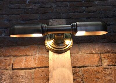 Lámpara de pared en la que hay dos puntos de luz de metal y de color negro